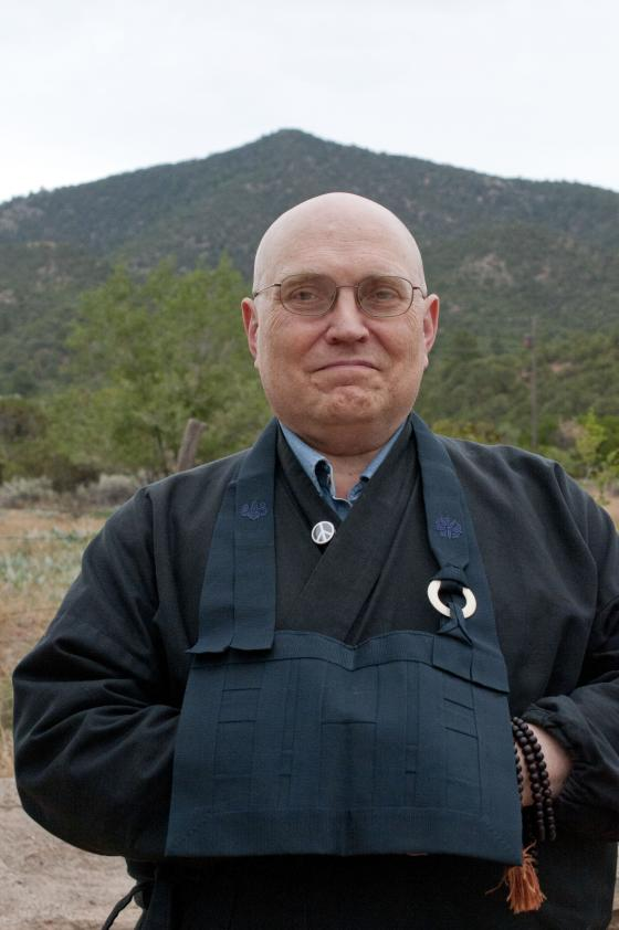 Zen priest Teigen Leighton in front of a green mountain